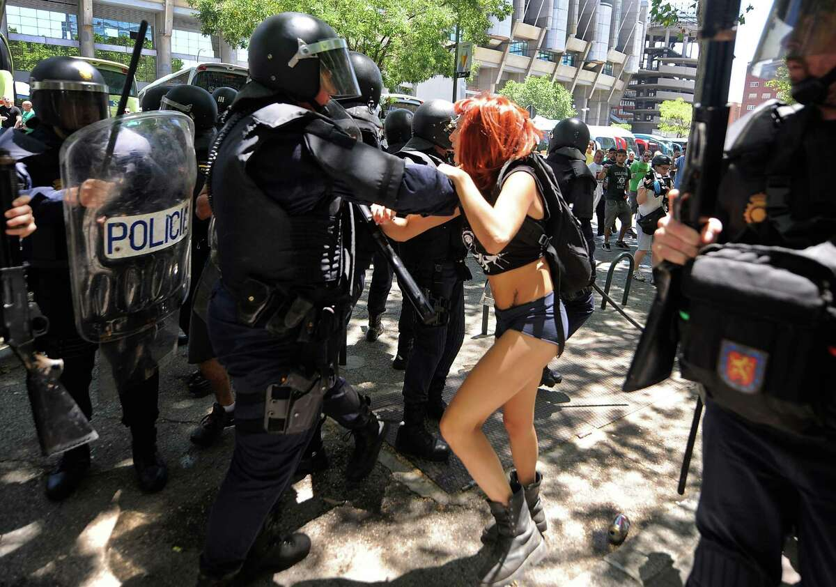 MADRID, SPAIN - JULY 11: A woman grapples with riot police during a demonstration by Spanish coal miners on July 11, 2012 in Madrid, Spain. The miners had marched to Madrid in protest at industry subsidy cuts.
