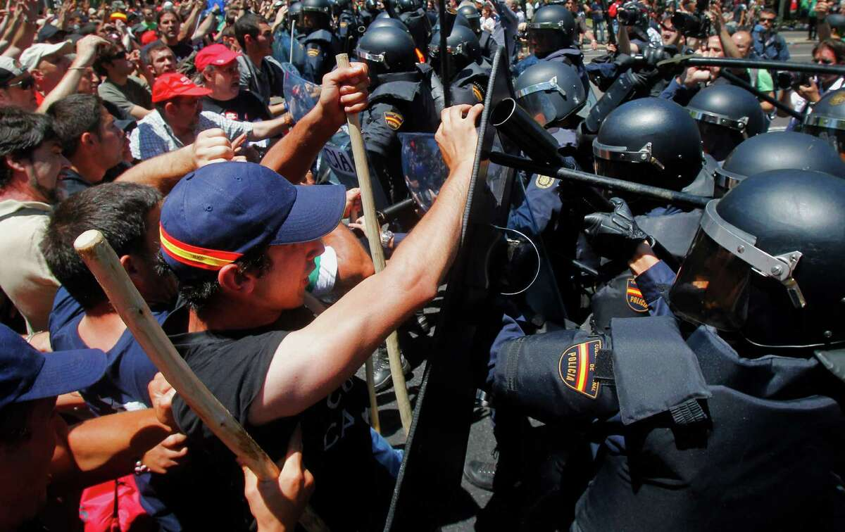 Demonstrators clash with riot police during the coal miner's march to the Minister of Industry's building in Madrid, Wednesday, July 11, 2012. The miners' march into the capital was the culmination for some of a nearly three-week trek from the regions where they eke out a living. Miners who walked 18 days from northern and eastern mining regions were received as heroes on Tuesday night as they entered the Puerta del Sol, one of the city's main plazas.
