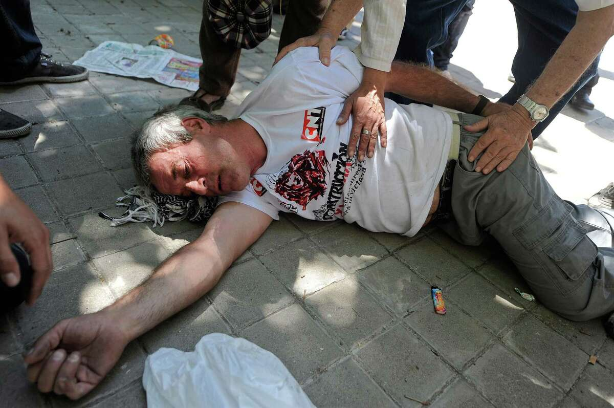 MADRID, SPAIN - JULY 11: A man is tended to by police after collapsing during a demonstration by Spanish coal miners on July 11, 2012 in Madrid, Spain. The miners had marched to Madrid in protest at industry subsidy cuts.