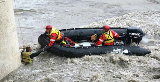 Santos Oliva, 26, is rescued Wednesday, July 11, 2012 from the San Antonio River at the Roosevelt Avenue overpass by firefighters from Station No. 11. Photo: William Luther, San Antonio Express-News / SAN ANTONIO EXPRESS-NEWS