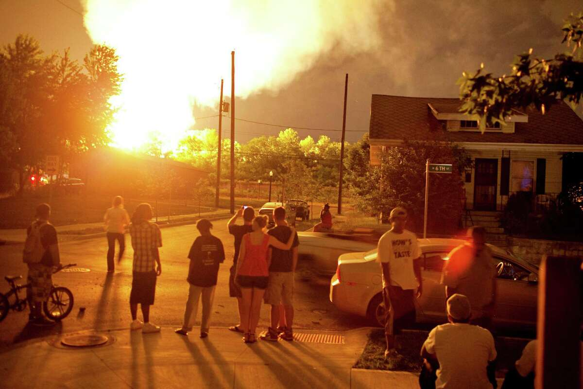People watch the flames shoot up from a freight train that derailed and some cars burst into flames, early Wednesday morning in Columbus Ohio. Lt. Terry Bush says the accident happened at about 2 a.m. Wednesday in a mixed-use part of the city, and people living in one-mile radius of the blast have been evacuated.