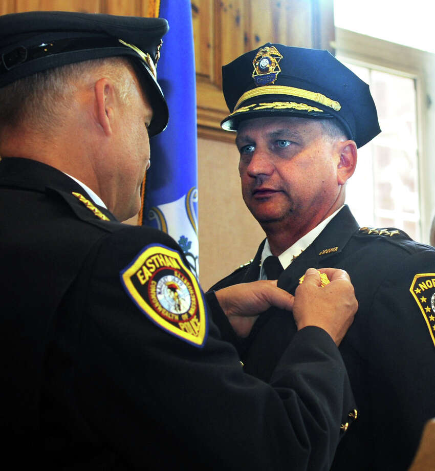 Thomas Kulhawik gets his badge from his brother, Edward Kulhawik, Eastham, Mass. Police Chief, as Thomas is sworn in as Norwalk Police Chief during a ceremony at Norwalk City Hall on Wednesday, July 11, 2012. Kulhawik will replace Harry Rilling, who resigned after serving in the department for 17 years. Photo: Lindsay Niegelberg / Stamford Advocate