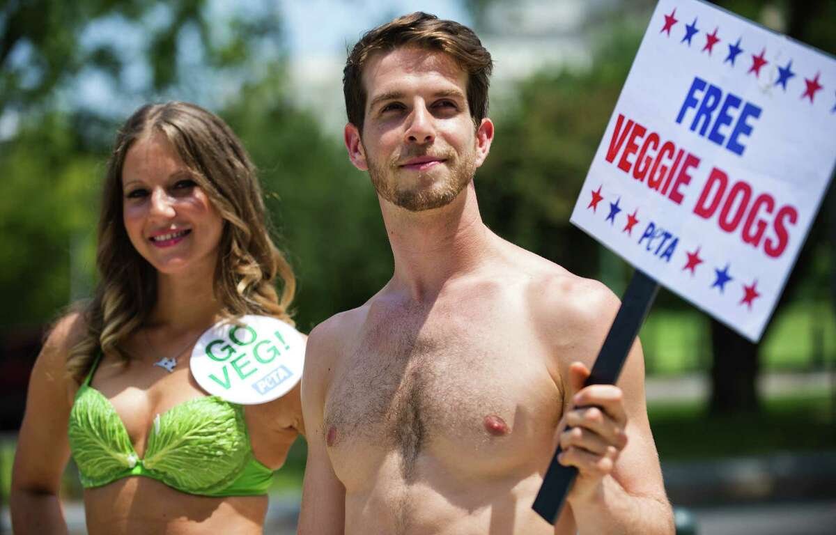 """On Capitol Hill, PETA's """"Sexy Lettuce Lady"""" and """"Banana Boy"""" give veggie hotdogs to members of Congress and their staff, July 11, 2012."""