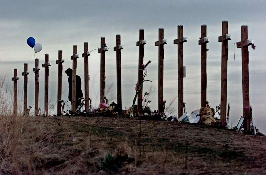 FILE - This April 28, 1999 file photo shows an unidentified woman with15 crosses posted on a hill above Columbine High School in Littleton, Colo. Wednesday, April 28, 1999 in remembrance of the 15 people who died during a school shooting on April 20. Sony Electronics and the Nielsen television research company collaborated on a survey ranking TV's most memorable moments. Other TV events include, the Sept. 11 attacks in 2001, Hurricane Katrina in 2005, the O.J. Simpson murder trial verdict in 1995 and the death of Osama bin Laden in 2011. (AP Photo/Eric Gay, file) Photo: ERIC GAY, Associated Press / AP1999