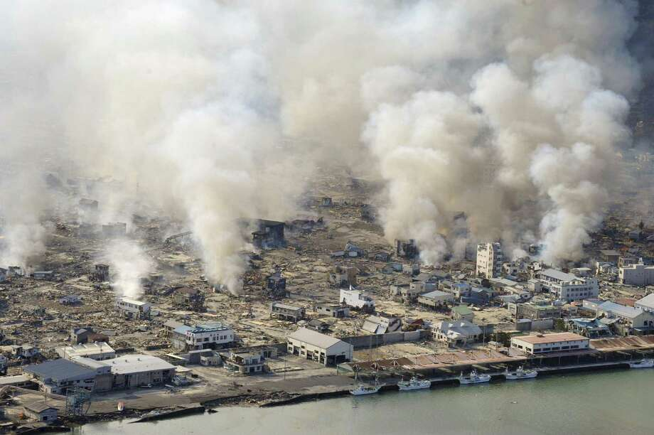 FILE - This March 12, 2011 file photo shows smokes rising from burning homes in Yamadamachi in Iwate Prefecture, northern Japan a day after a strong earthquake triggered a devastating tsunami in the area. Sony Electronics and the Nielsen television research company collaborated on a survey ranking TV's most memorable moments. Other TV events include, the Sept. 11 attacks in 2001, Hurricane Katrina in 2005, the O.J. Simpson murder trial verdict in 1995 and the death of Osama bin Laden in 2011. (AP Photo/Kenji Shimizu, The Yomiuri Shimbun)  JAPAN OUT, CREDIT MANDATORY Photo: Kenji Shimizu, Associated Press / 2011 AP