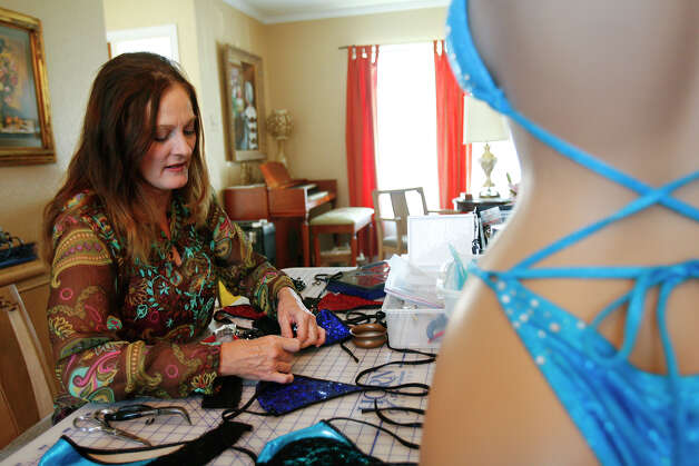 Carrie Harrell adds decorative elements to her LollieRocks one-of-a-kind bikinis last year. Harrell, of San Antonio, and her daughter, who lives in Houston, founded the swimwear design firm two years ago. Photo: SALLY FINNERAN / sfinneran@express-news.net