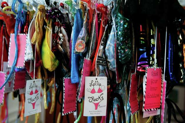One-of-a-kind Lollie Rocks bikinis hang in Carrie Harrell's studio. Last year, Harrell and her team kept busy when they customized 37 bikinis for contestants at the Miss Texas pageant. The company focuses mainly on competition swimwear. Photo: SALLY FINNERAN / sfinneran@express-news.net