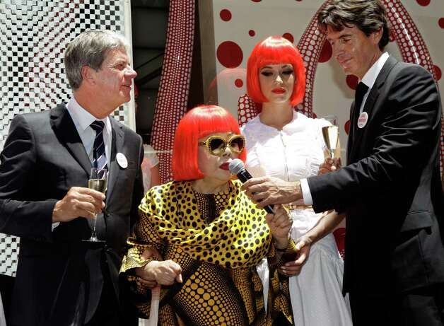 A model poses beside Japanese artist Yayoi Kusama, center, Louis Vuitton CEO Yves Carcelle, far left, and Vuitton second-in-command Jordi Konstans in front of the windows Kusama helped design at Vuitton's flagship Fifth Avenue store for the unveiling of a new collaborative collection by Kusama and Vuitton creative director Marc Jacobs in New York, Tuesday, July 10, 2012.  (AP Photo/Kathy Willens) Photo: Kathy Willens, STF / AP