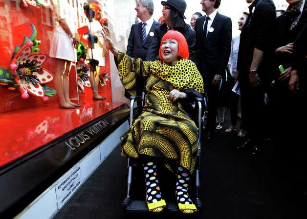 Artista Yayoi Kusama, center poses for photographers with Louis Vuitton CEO Yves Carcelle, upper left, in front of the windows of Vuitton's flagship store for the unveiling of a new collaborative collection by Vuitton creative designer Marc Jacobs and Kusama in New York, Tuesday, July 10, 2012.  (AP Photo/Kathy Willens) Photo: Kathy Willens, STF / AP