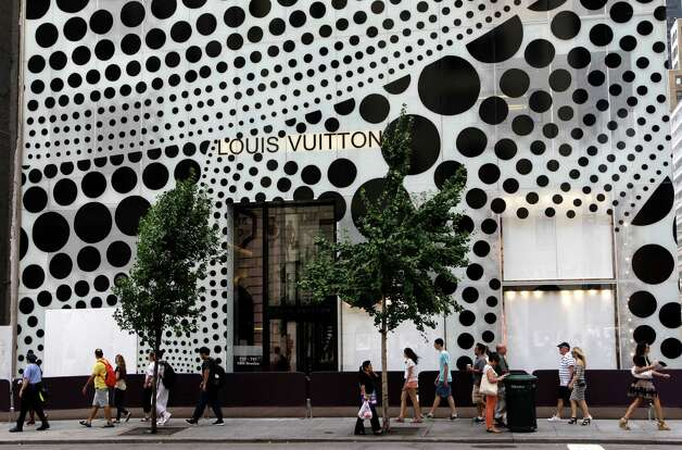 Pedestrians walk in front of Louis Vuitton's flagship Fifth Avneue store in New York, Tuesday, July 10, 2012, before the company unveiled windows and a collection collaboratively designed by Japanese artist Yayoi Kusama and  Vuitton creative director Marc Jacobs.  (AP Photo/Kathy Willens) Photo: Kathy Willens, STF / AP