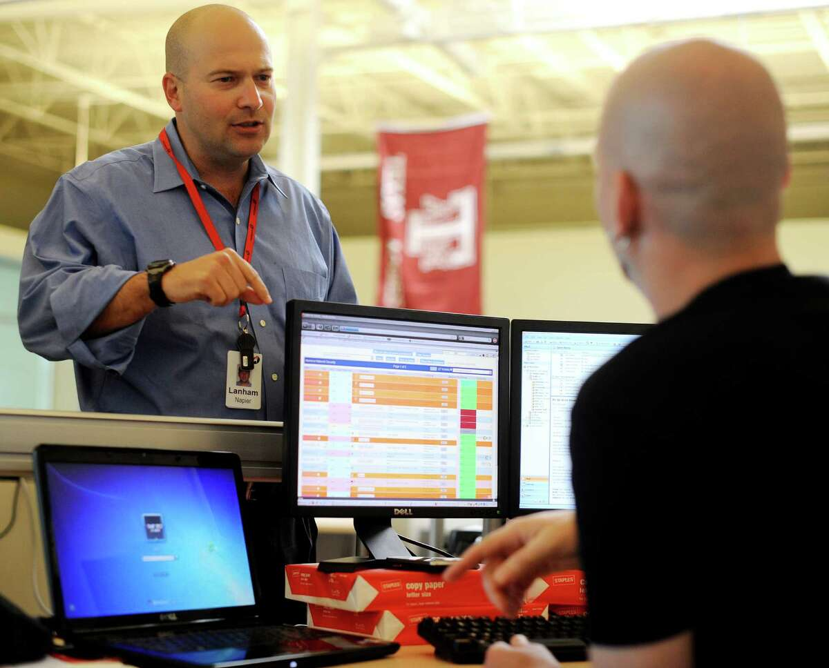 Lanham Napier, left, CEO of Rackspace Hosting Inc., chats with employee Jon Gilyeat in the company's headquarters on Tuesday, April 27, 2010. BILLY CALZADA / gcalzada@express-news.net