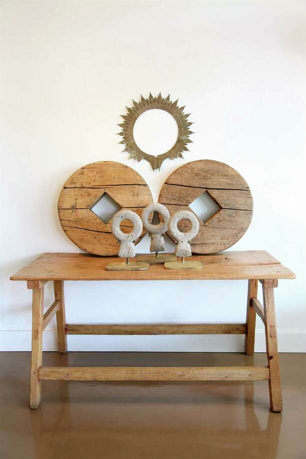 Hacienda Style carries this antique sabino (Mexican cypress) ranch table with stone horse ties (newly mounted as sculptural accents on iron stands), old wooden wheels and antique metal corona. Photo: Courtesy, Hacienda Style