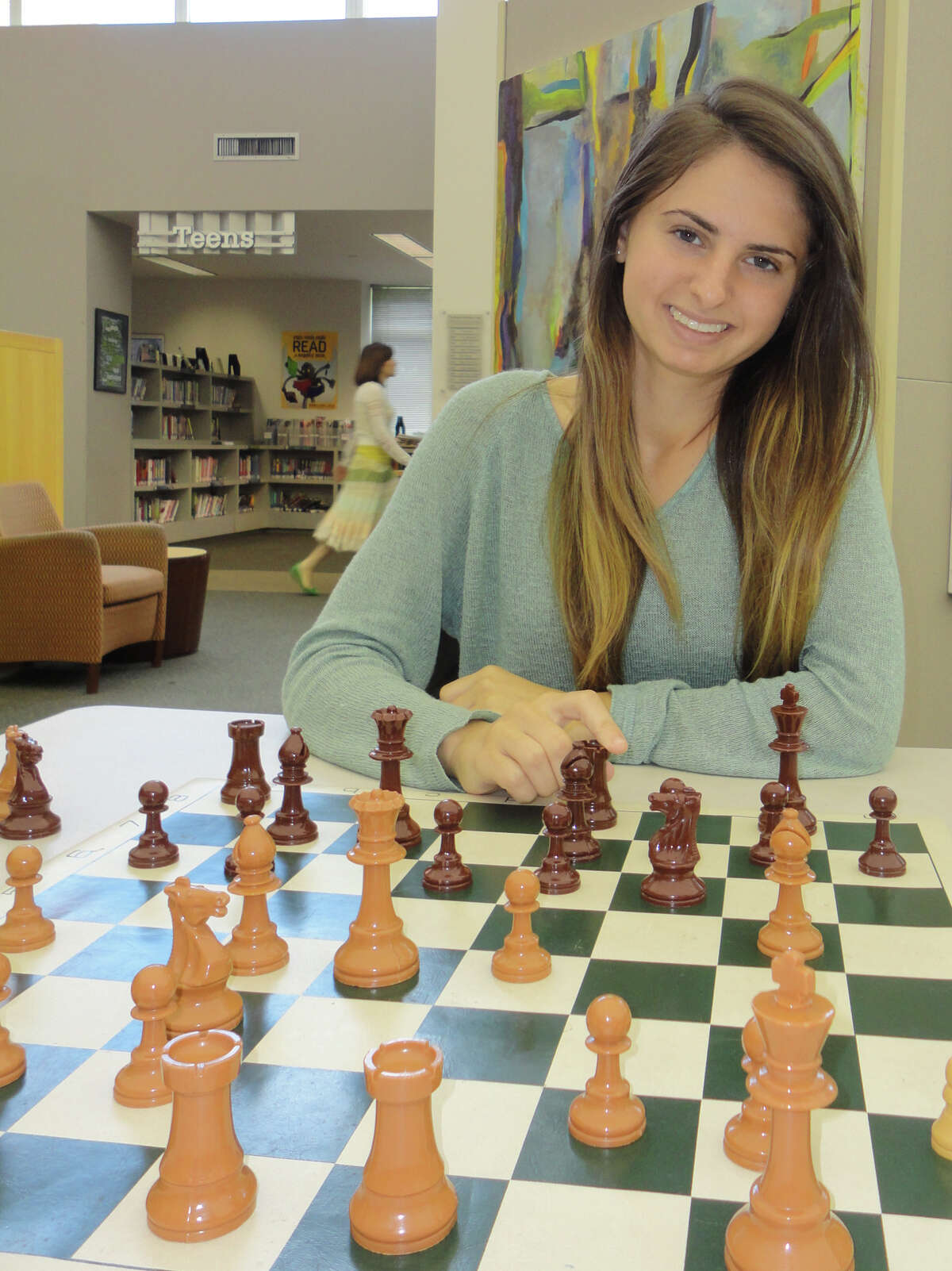 Alexandra Wiener, an 18-year-old recent graduate of Staples High School, practices chess strategy at the Westport Public Library. She already has several national and state chess championship titles to her credit.
