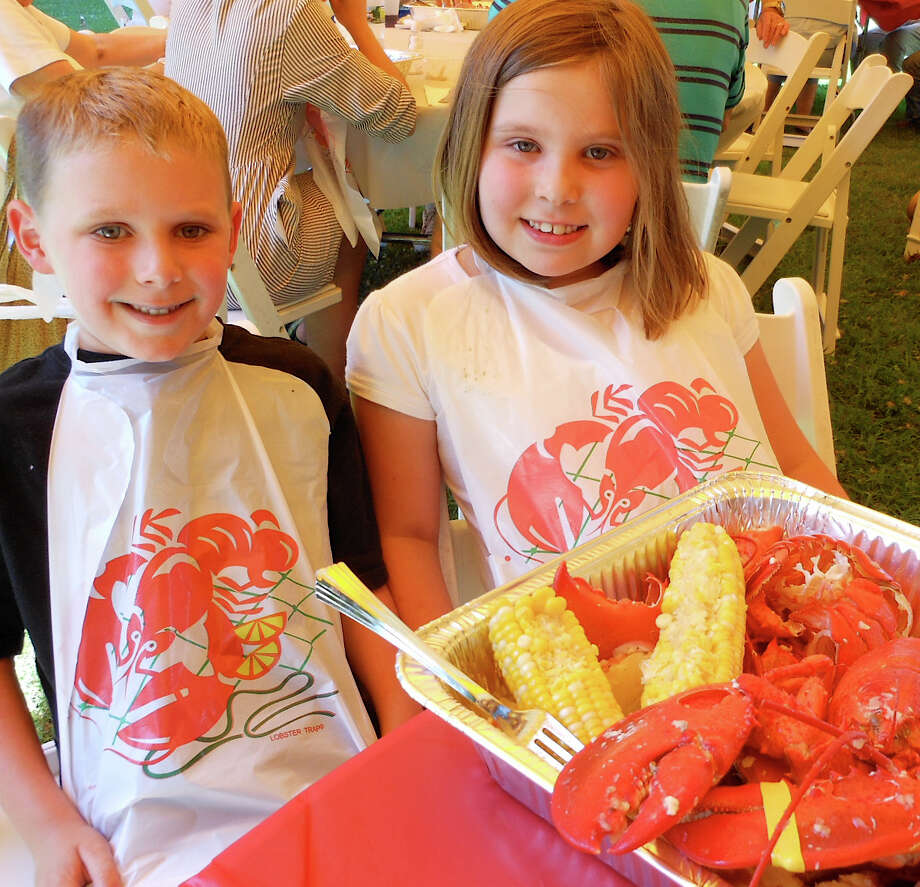 Joey and Sydney Rainis of Fairfield enjoy lobster and corn at St. Anthony of Padua Church's annual picnic on Sunday. Photo: Mike Lauterborn / Fairfield Citizen contributed