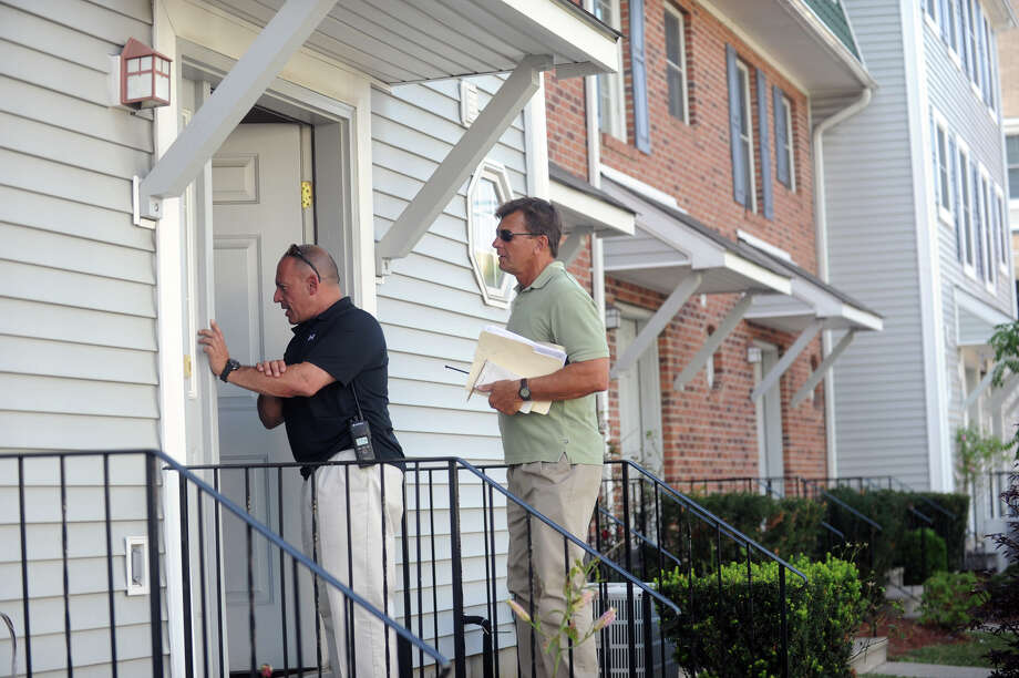 Stamford Police investigators Frank Laccona and Paul Guzda talks to a resident on Spruce Street in Stamford, Conn., July 11, 2012. Investigators suspect this to be the scene where Wyclif Bel-Jean, 21, was killed early Wednesday morning. Bel-Jean was later found near Norwalk Hospital suffering of an apparent gunshot wound. Police believe the shooting is related to the early Sunday morning shooting of 22-year-old Darius Jones on Custer Street. Photo: Keelin Daly / Stamford Advocate