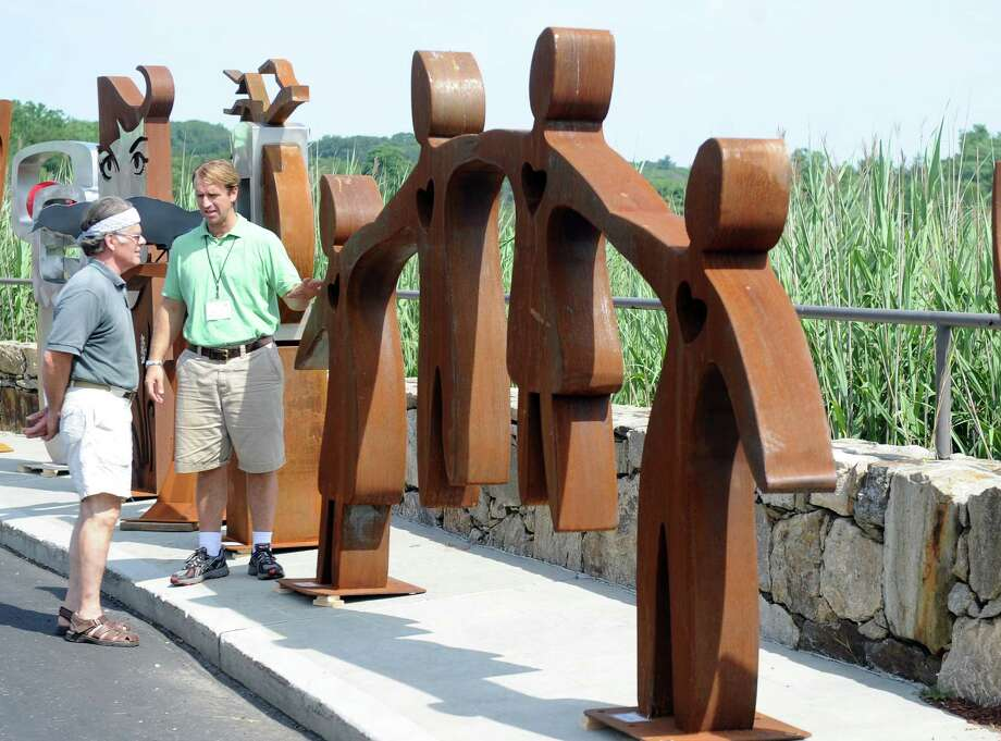 Artist Dale Rogers talks about his work with Bryan Kenney, during last year's 38th annual Fine Arts Festival in Westport, Conn. The event, which is presented by the Westport Downtown Merchants Association, is returning for its 39th year, Saturday and Sunday, July 21 to 22, 2012, at Parker Harding Plaza and Gorham Island. Rogers is expected to be among the more than 140 artists who will be participating in the event. Photo: Autumn Driscoll, ST / Connecticut Post