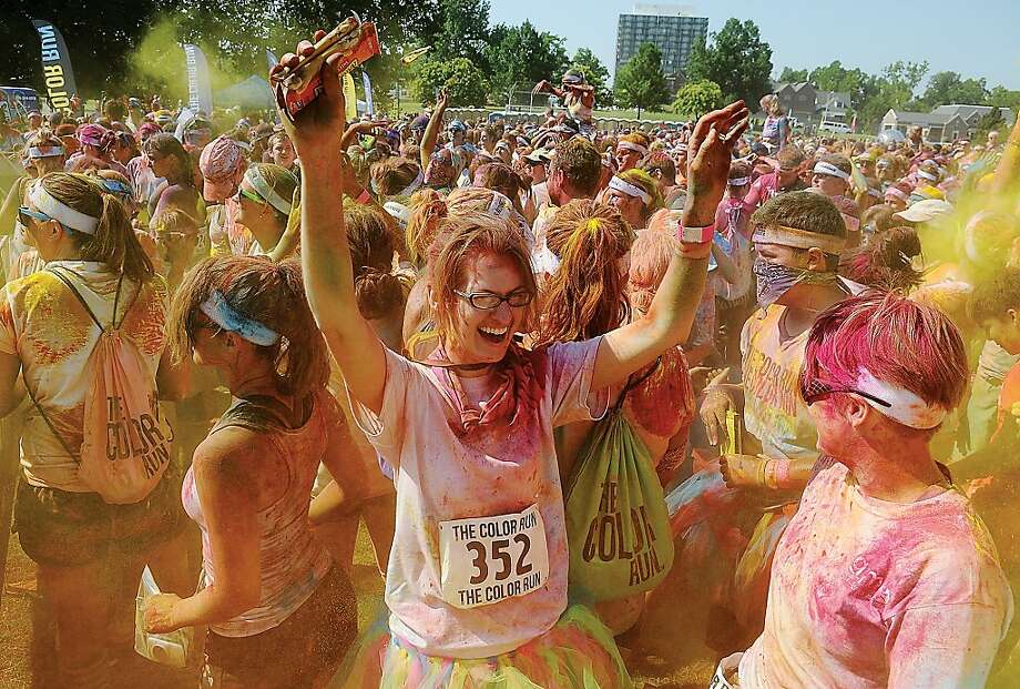 Enid, Okla. runners Grace Musgrave, center, and Heidi Andersen, right, are showered with yellow paint powder during The Color Run 5K Saturday, June 23, 2012 at Veterans Park in Tulsa, Okla. More than 10,000 runners and walkers participated in the annual fundraising event for the River Park Foundation. (AP Photo/Enid News And Eagle, Bonnie G. Vculek) Photo: Bonnie G. Vculek, Associated Press