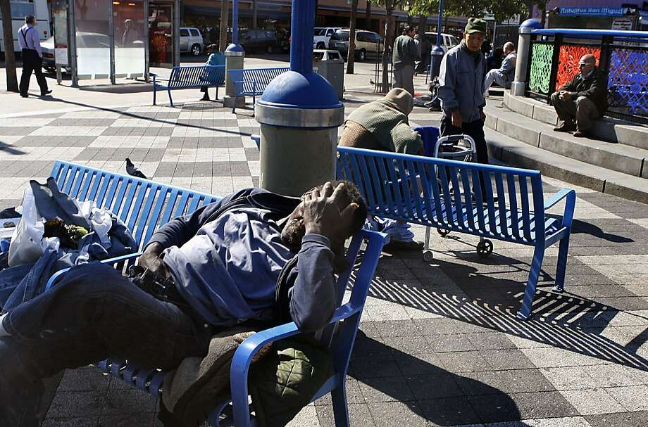 A man taking a nap on a bench with his belongings on the street level plaza of the Bart station on Mission at 16th streets in San Francisco. Photo: Liz Hafalia, The Chronicle