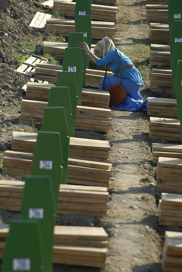 A Bosnian Muslim woman weeps near the grave of her relative among the graves of Srebrenica victims at the Memorial Cemetery in Potocari, near Srebrenica, 160 kms northeast of Sarajevo, Bosnia, Wednesday, July 11, 2012. Thousands gathered in the cemetery for the mass burial of 520 bodies, marking the 17th anniversary of the Srebrenica massacre. (AP Photo/Sulejman Omerbasic) Photo: Sulejman Omerbasic, Associated Press