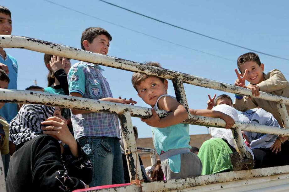 Syrian children ride in the back of a truck as they return to their village of Kfar Sijna on Tuesday, the day after it came under fire by Syrian government forces. Photo: LO / AFP