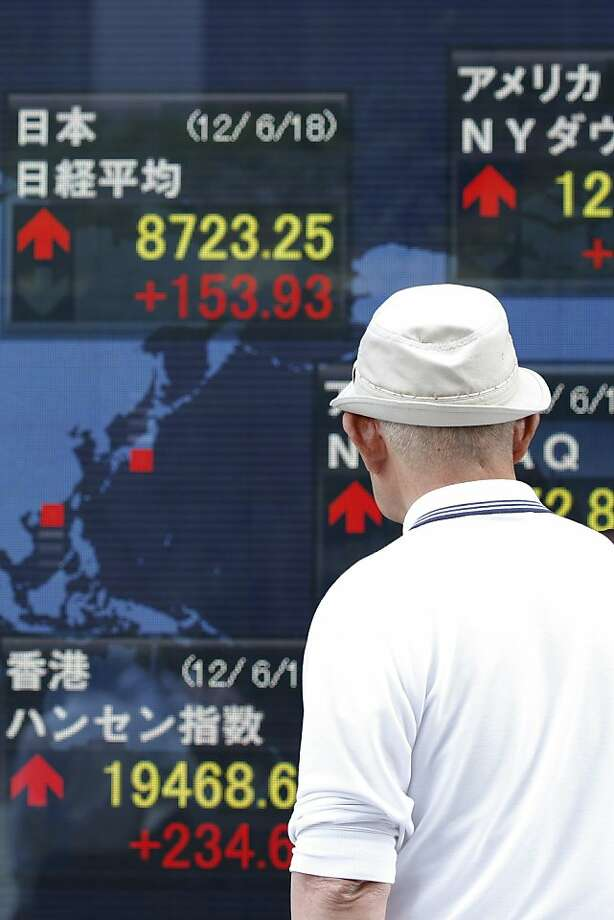 A man looks at an electronic stock board displaying the Nikkei 225 Stock Average figures outside a securities firm in Tokyo, Japan, on Monday, June 18, 2012. Asian stocks and the euro rose to the highest levels in a month, and commodities climbed as gains by pro-bailout parties in Greek elections eased concern the nation would exit the euro. Photographer: Kiyoshi Ota/Bloomberg Photo: Kiyoshi Ota, Bloomberg