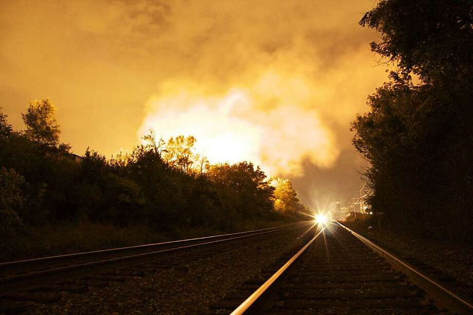 Flames rise from a derailed freight train, left unseen,   early Wednesday July 11, 2012 in Columbus Ohio.  Part of a freight train derailed and caught fire in Ohio's capital city early Wednesday, shooting flames skyward into the darkness and prompting the evacuation of a mile-wide area as firefighters and hazardous materials crews worked to determine what was burning and contain the blaze.(AP Photo/Chris Mumma) Photo: Chris Mumma, Associated Press