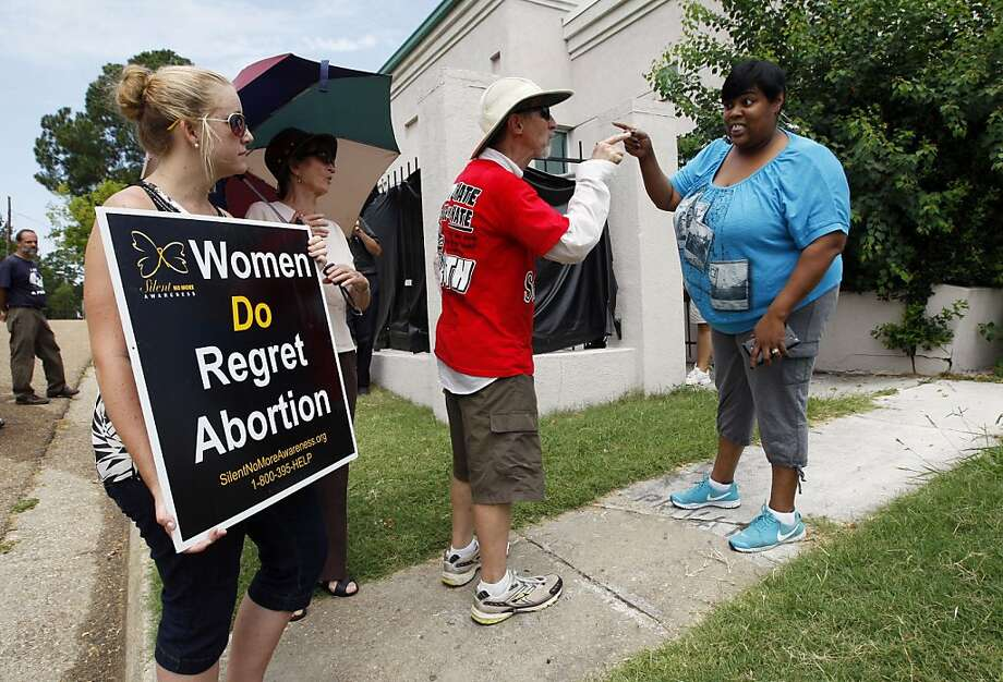 Abortion opponents Ron Nederhoed, center, and Ashley Sigrest, right, argue with the Jackson Women's Health Organization's administrator Shannon Brewer, right, over the opponent's trespassing onto the property of Mississippi's only abortion clinic in Jackson, Miss., Monday, July 2, 2012, after a federal judge issued a temporary restraining order Sunday, that blocked enforcement of a law that could regulate the clinic out of business. The law would require any physician doing abortions at the clinic to be an OB-GYN with privileges to admit patients to a local hospital. (AP Photo/Rogelio V. Solis) Photo: Rogelio V. Solis, Associated Press
