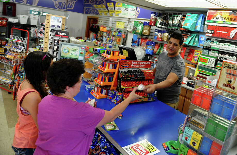 Shop Smart Store Manager Yaser Butt sells a lottery ticket to Teresa Ramos, of Seymour, in Seymour, Conn. on Wednesday July 11, 2012. A local Seymour couple has won the lottery and bought their ticket ffrom a local deli. Shop Smart has sold a winning lottery ticket in the past. Photo: Christian Abraham / Connecticut Post