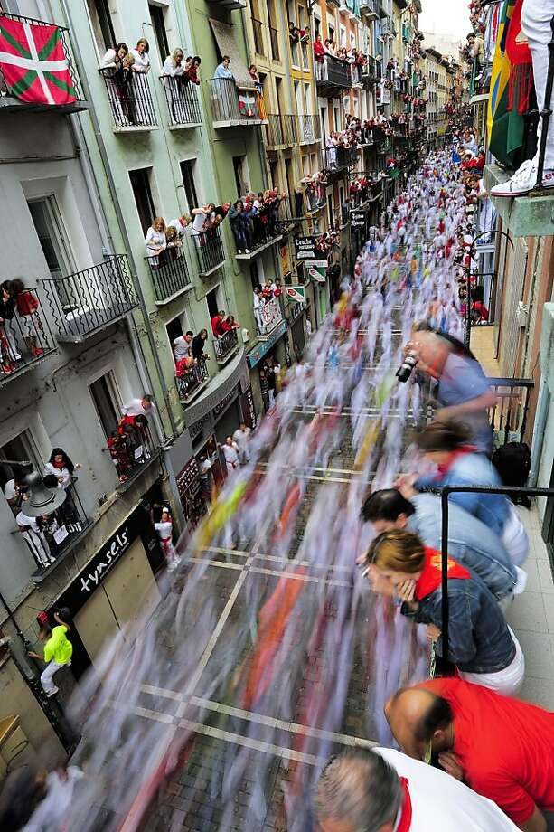 Revelers run on Estafeta street beside to Fuente Ymbro fighting bulls ranch as people look on from balconies above, during the fifth running of the bulls, at the San Fermin fiestas, in Pamplona, northern Spain, Wednesday, July 11, 2012. (AP Photo/Alvaro Barrientos) Photo: Alvaro Barrientos, Associated Press