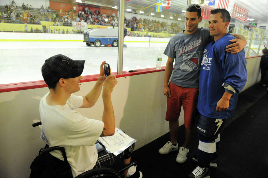 Stathi Hasiotis snaps a shot of hockey player Martin St. Louis and his brother, Pete Hasiotis, during the Big Assist IV ice hockey exhibition game to benefit the Obie Harrington-Howes Foundation at Terry Conners Ice Rink in Stamford, Conn., July 11, 2012. Photo: Keelin Daly / Stamford Advocate