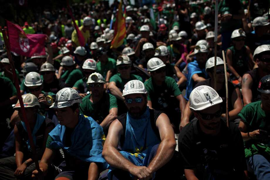 Coal miners arrive near Spain Industry Ministry after marching up Madrid's main north-south avenue on Wednesday July 11, 2012.  Riot police fired rubber bullets Wednesday at Spanish coal miners protesting in the streets of Madrid over subsidy cuts they fear will jeopardize their meager livelihood. The miners' march into the capital was the culmination for some of a nearly three-week trek from the regions where they eke out a living.  (AP Photo/Emilio Morenatti) Photo: Emilio Morenatti