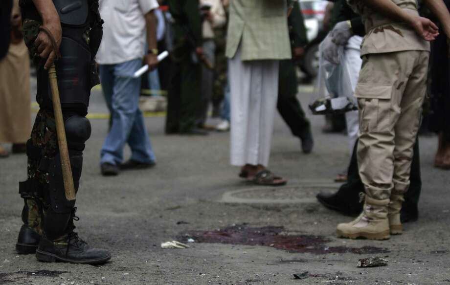 A Yemeni soldier, left, stands next to the blood of police cadets who were killed in a suicide bomb attack at a police academy in Sanaa, Yemen, Wednesday, July 11, 2012. A suicide bomber threw himself into a crowd of Yemeni police cadets leaving their academy on Wednesday and detonated his explosives, killing several people, a security official said.(AP Photo/Hani Mohammed) Photo: Hani Mohammed