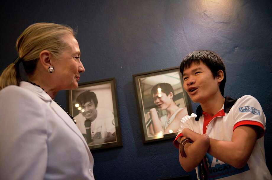 U.S. Secretary of State Hillary Rodham Clinton, left, greets Phongsavath Souliyalat, who lost his forearms and sight from a blast of an unexploded bomb left since Vietnam War while she tours the Cooperative Orthotic Prosthetic Enterprise Center (COPE), in Vientiane, Laos, July 11, 2012. COPE provides free prosthetics to those who need them including the victims of blasts of unexploded Vietnam War era ordnance,  (AP Photo/Brendon Smialowski, Pool) Photo: Brendan Smialowski