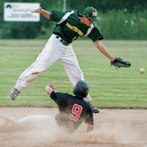 New Milford's Matt Rodriguez jumps to avoid a sliding Matt Burger of New Canaan, at second, during a game in the Cal Ripken 12 year old league played at Mitchell Park in Bethel. Wednesday, July 11, 2012 Photo: Scott Mullin