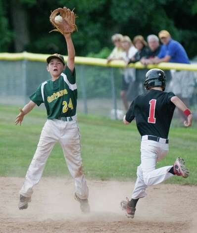 New Milford's Colin Lindner tries to get the throw before New Canaan's Jim Stanley gets to first base in a Cal Ripken 12 year old league game played at Mitchell Park in Bethel. Wednesday, July 11, 2012 Photo: Scott Mullin / The News-Times Freelance
