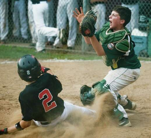 New Canaan's Justin Stemerman slides into home before New Milford's Derek Profita gets the throw in a Cal Ripken 12 year old league game played at Mitchell Park in Bethel. Wednesday, July 11, 2012 Photo: Scott Mullin