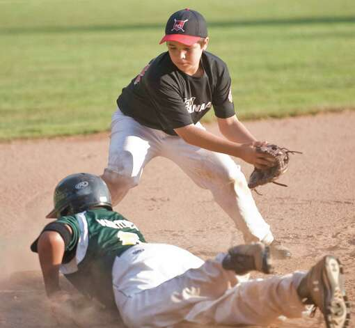 New Milford's Mitch Cavaliere dives back to third before New Canaan's Mike Pelli can apply the tag in a Cal Ripken 12 year old league game played at Mitchell Park in Bethel. Wednesday, July 11, 2012 Photo: Scott Mullin / The News-Times Freelance