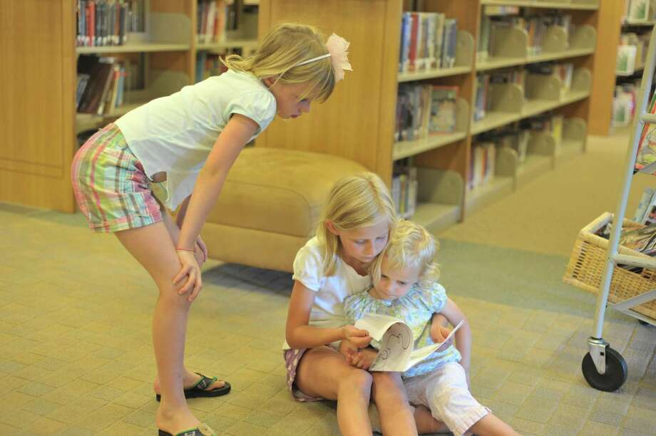 Kate Lane, 9, reads to her little sisters Charlotte, 3, and Avery, 7, at the Darien Library, July 9, 2012. Photo by Henry Eschricht, Darien, Conn. Photo: Contributed Photo