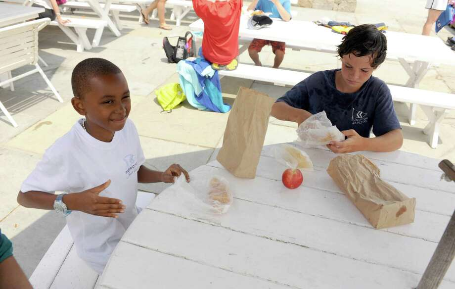 Kobe Tucker, 10, enjoys lunch with Chase Daley, age 12, at Noroton Yacht Club Wednesday, July 11, 2012. Kobe is visiting the Daleys as part of the Fresh Air Fund. Photo by Harrison Thompson, Darien, Conn. Photo: Contributed Photo