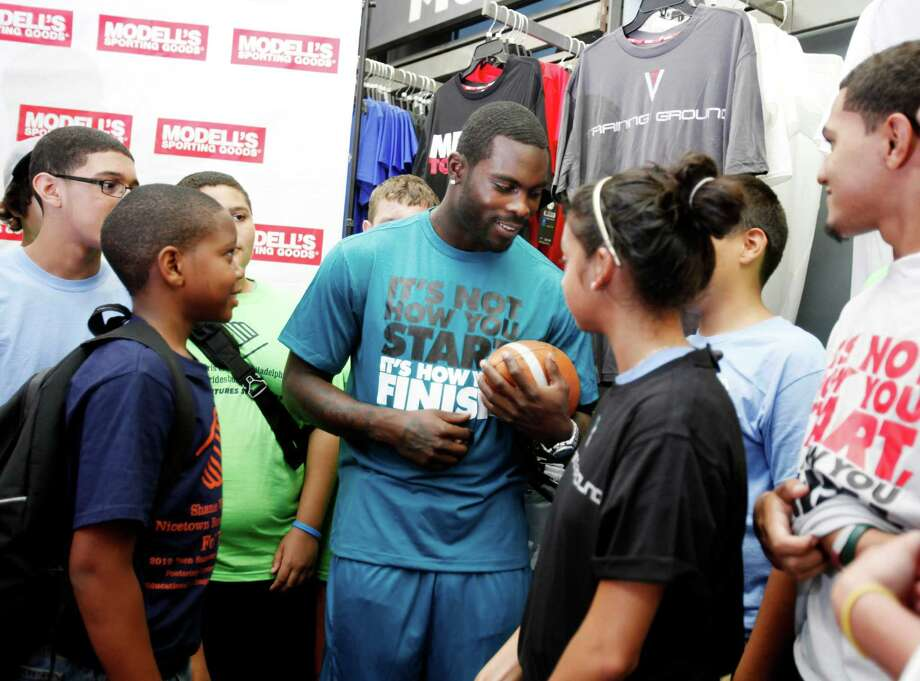 Philadelphia Eagles quarterback Michael Vick, center, talks to members of the Boys & Girls Club of Philadelphia about his new V7 apparel line at Modellís Sporting Goods, Wednesday, July 11, 2012, in Philadelphia. The clothing line called V7 and will be sold exclusively at East Coast sporting goods shop Modell's. (AP Photo/Brynn Anderson) Photo: Brynn Anderson / AP