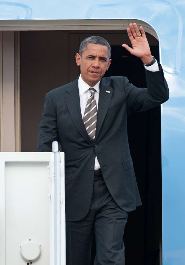President Barack Obama waves as he exits Air Force One at Andrews Air Force Base, Md., Tuesday, July 10, 2012. (AP Photo/Cliff Owen) Photo: Cliff Owen / FR170079 AP