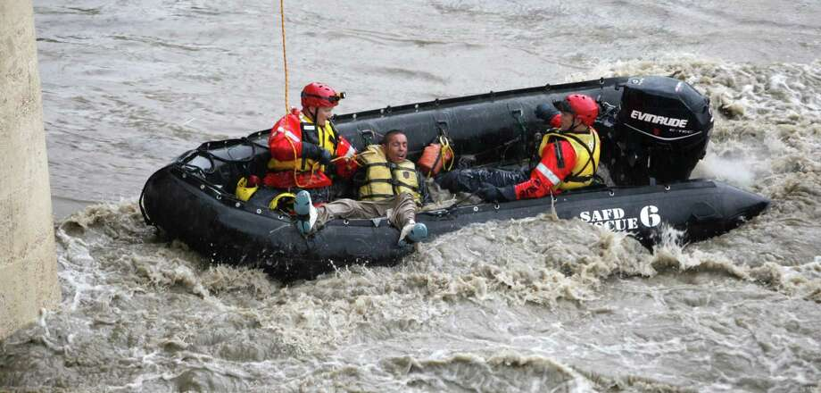 Santos Olivo, 26, is rescued by firefighters Wednesday from the San Antonio River at a downtown overpass. He had been sleeping on the bank when the river rose suddenly and left him clinging to a bridge support. Flash flooding closed part of Interstate 35 during the morning commute. Photo: William Luther / SAN ANTONIO EXPRESS-NEWS