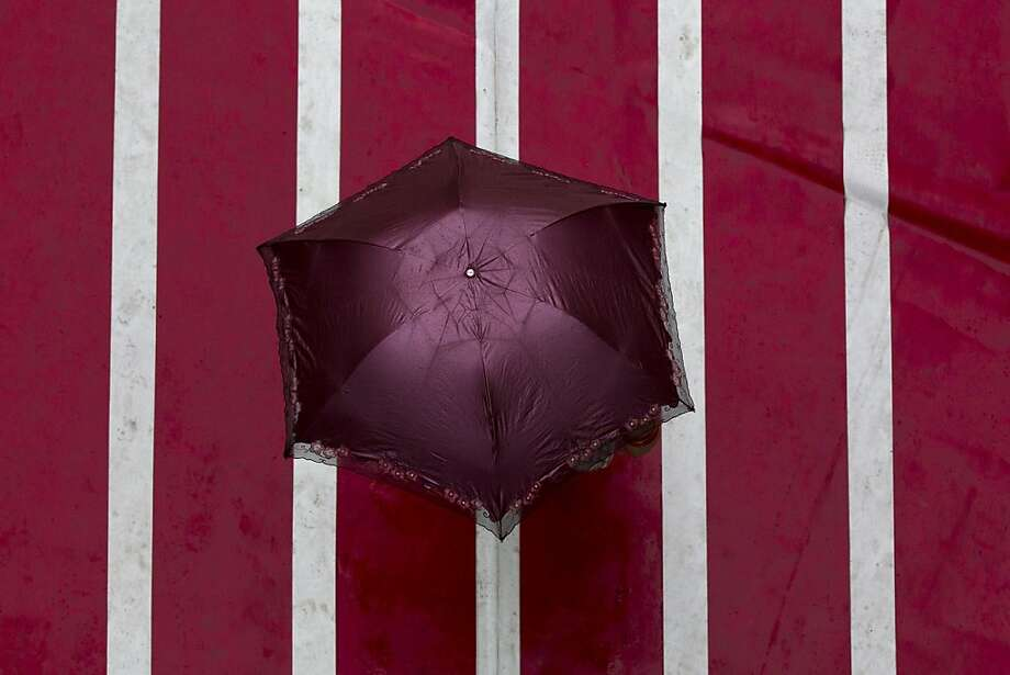 A woman holds an umbrella while walking on a carpet featuring athletic runway tracks outside a shopping mall in a rain in Beijing, China, Wednesday, July 11, 2012. (AP Photo/Alexander F. Yuan) Photo: Alexander F. Yuan, Associated Press