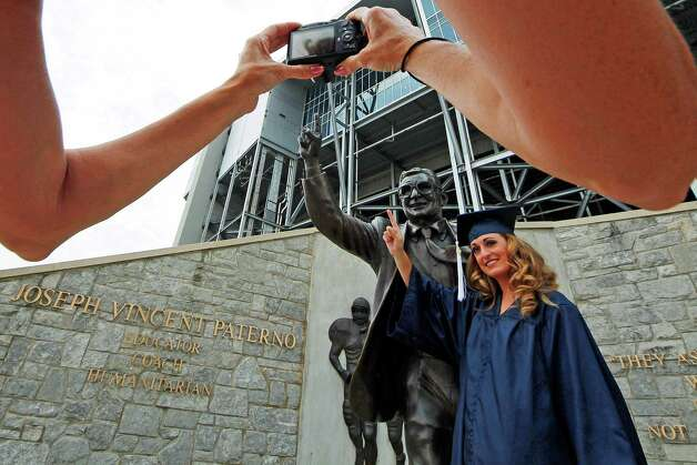 Gina DiJohnson, who will graduate from Penn State University in three weeks, poses for a picture with a statue of former Penn State Football coach Joe Paterno  outside Beaver Stadium on the Penn State campus Wednesday, July 11, 2012. The Freeh Report on the Jerry Sandusky child sex scandal at Penn State will be released Thursday morning. (AP Photo/Gene J. Puskar) Photo: Gene J. Puskar