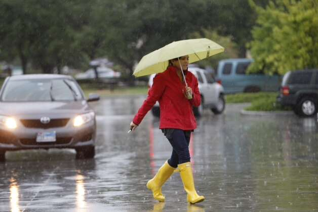 Umbrellas come out Thursday, July 12, 2012, as rains continue falling in Houston. Photo: Michael Paulsen, Michael Paulsen / Chronicle / Houston Chronicle