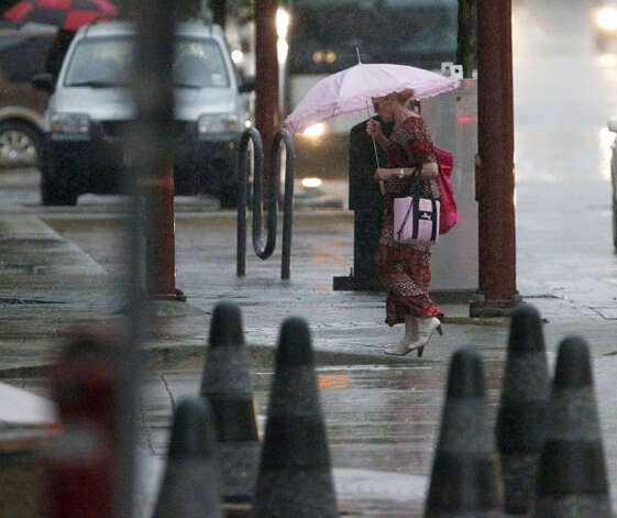 Pedestrians walk through the rain during the morning work commute Thursday, July 12, 2012, in Houston. Photo: James Nielsen, ( James Nielsen / Chronicle ) / © Houston Chronicle 2012
