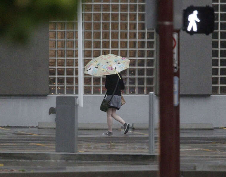 Pedestrians walk through the rain during the morning work commute Thursday, July 12, 2012, in Housto
