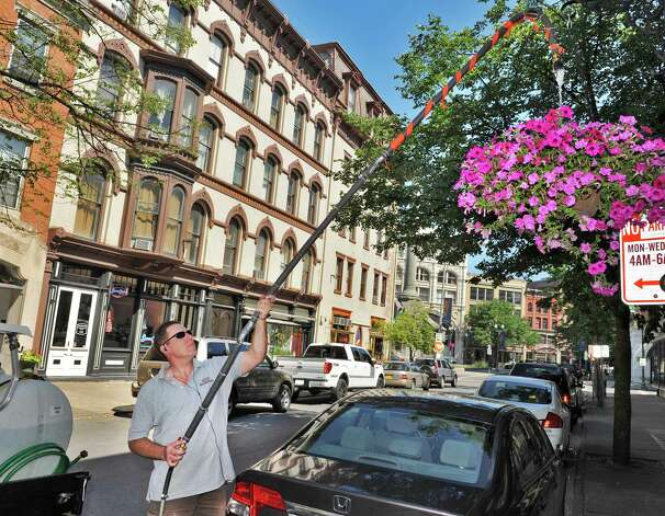 Rome Romagnoli of the Troy Business Improvement District waters hanging flower baskets along 2nd Street in Troy Wednesday July 11, 2012.    (John Carl D'Annibale / Times Union) Photo: John Carl D'Annibale