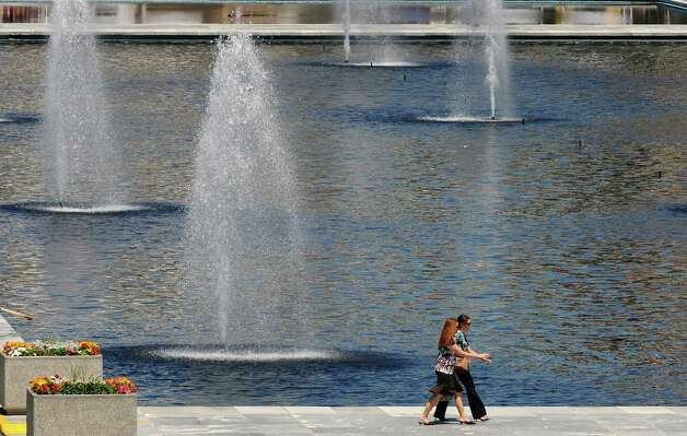 Pedestrians walk past the fountains of the Empire State Plaza  on Wednesday  July 11, 2012 in Albany, NY. (Philip Kamrass / Times Union) Photo: Philip Kamrass