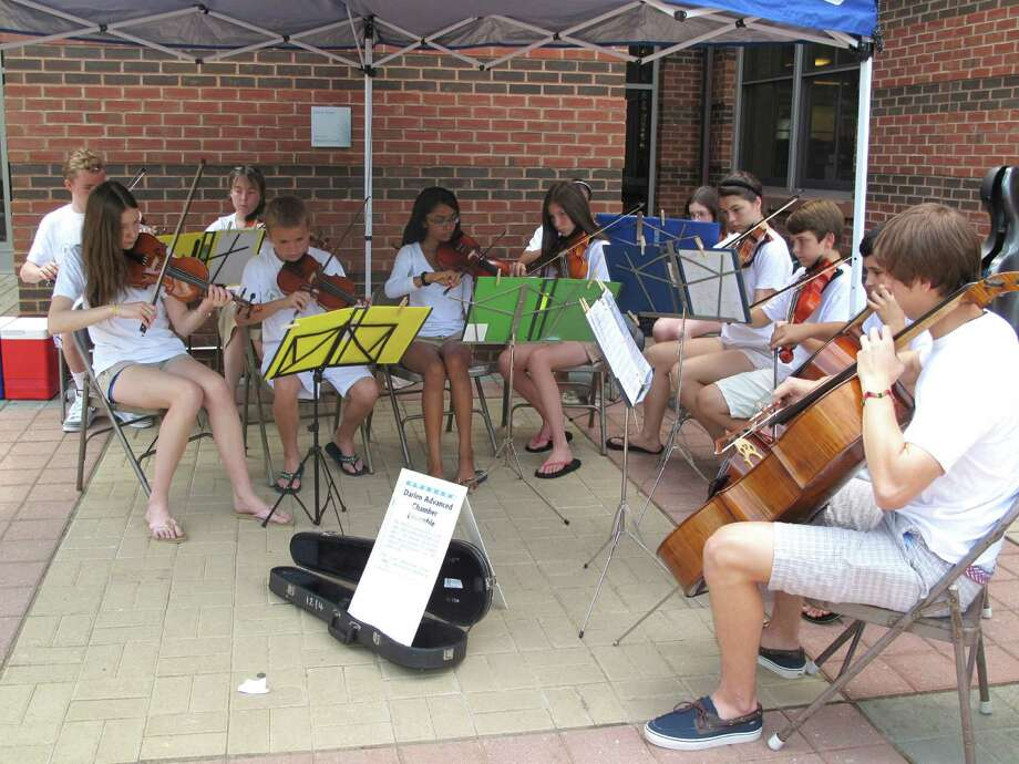 The Darien Summer Strings, part of the five-week Darien Summer School, performs numbers like ìI Canít Get No Satisfactionî by the Rolling Stones and ìGod Bless Americaî in the Darien Library courtyard Friday, July 6, 2012. They will also play at the DCA Thrift Shop July 13 and Darien Farmers Market July 18 and 25. In back (from left), Dylan Gilhooly, director Jane Minnis, Kristen Franco and Escher Campanella. In front (from left), Molly Petner, Connor Gonzalez-Falla, Ursula Patel, Elizabeth Petner, Adrienne Dean, Austin Hagander, Jake Morro and Jeffrey Gebauer. Darien, Conn. Photo: Thomas Michael